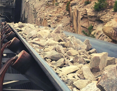 Conveyor belt hauling large brown rocks.