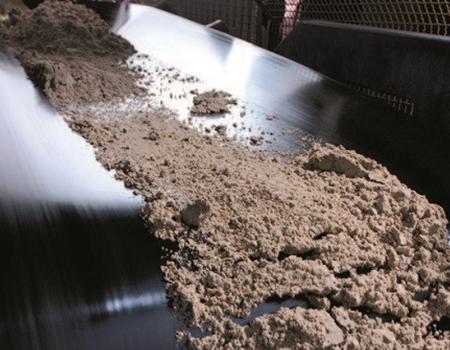 Brown powder being transported on conveyor belt.