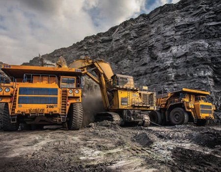 Three orange-colored heavy equipment vehicles working in a quarry.